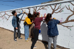 YHS students paint hand prints on mural.