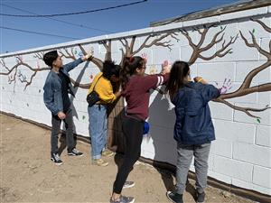 YHS students paint hand prints on mural