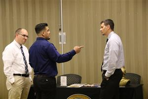 Assistant principal Mike Fritz and Principal Derek Bosch talk to a candidate at the job fair.