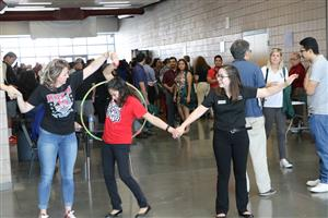 Staff members participate in a hula hoop game at the Kick off.