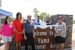 Gina Thompson, Norm Champagne, and others show off the Welcome to Yuma International Airport sign