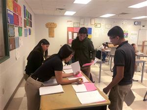 Students work on knowledge exam during construction competition