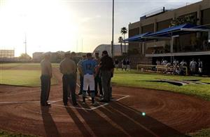 Coaches and MCAS personnel meet at home plate.