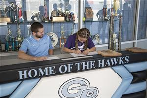 Corners signs her letter of intent with coach Briar Ploude looking on.